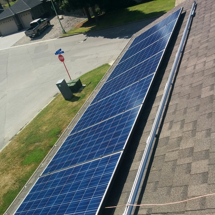 first row of two of blue polycrystalline solar electric panels mounted to asphalt roof.