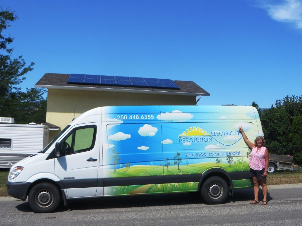 white van with decals depicting green hills and blue sky parked in front of a home recently fitted with solar electric.