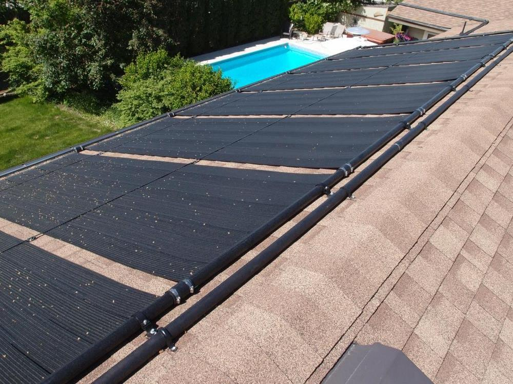 black solar panels mounted on a brown asphalt roof providing heating for the swimming pool below.