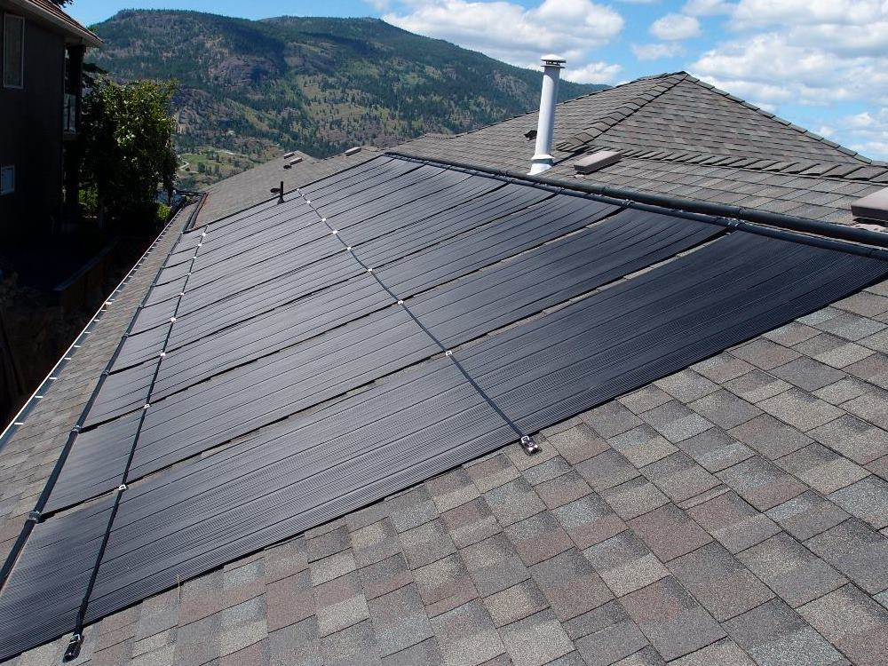 ten large black polypropylene solar panels fitted to house roof are secured with plastic covered stainless steel strapping.