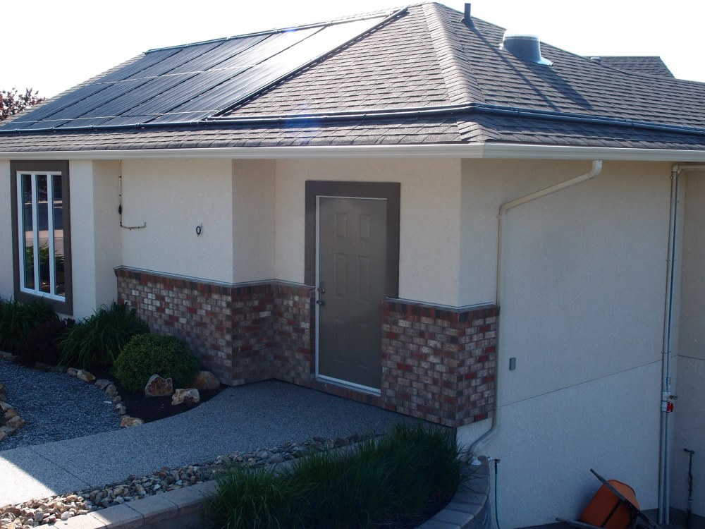 large black PVC solar pool panels are located on the house roof, helping to keep the pool warm and the house cool.