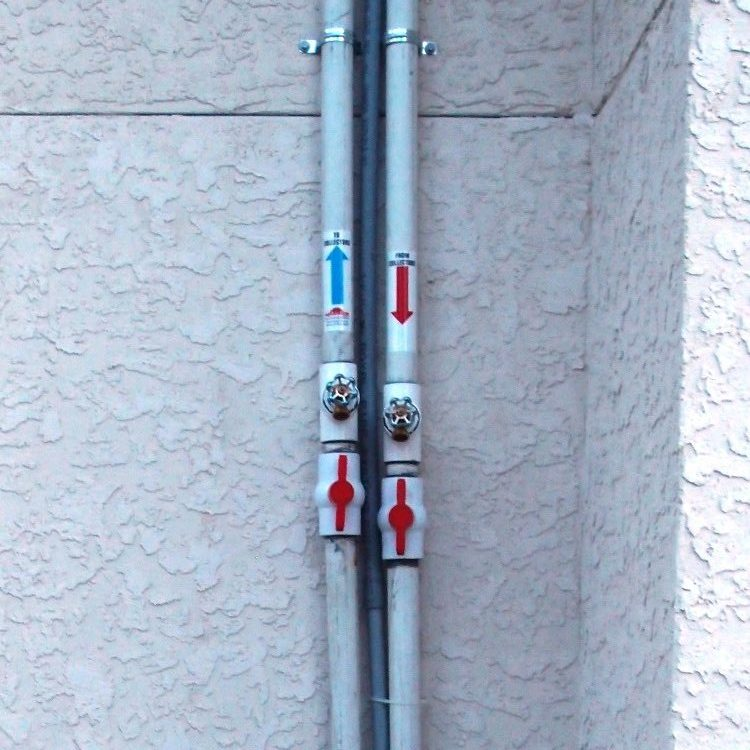 two white PVC valves located below two water spigots make winterizing the solar pool heater easy.